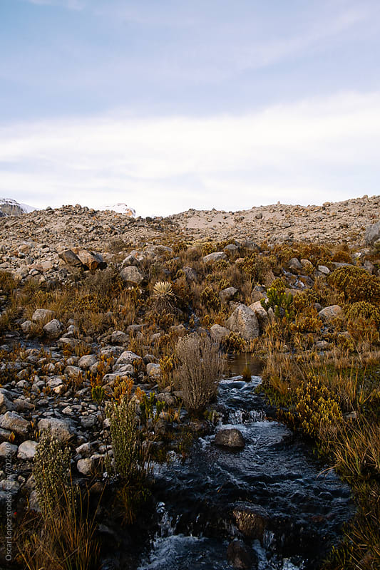 Creek on a glacial Plateau with Snowcapped Peaks by Oscar Lopez for Stocksy United