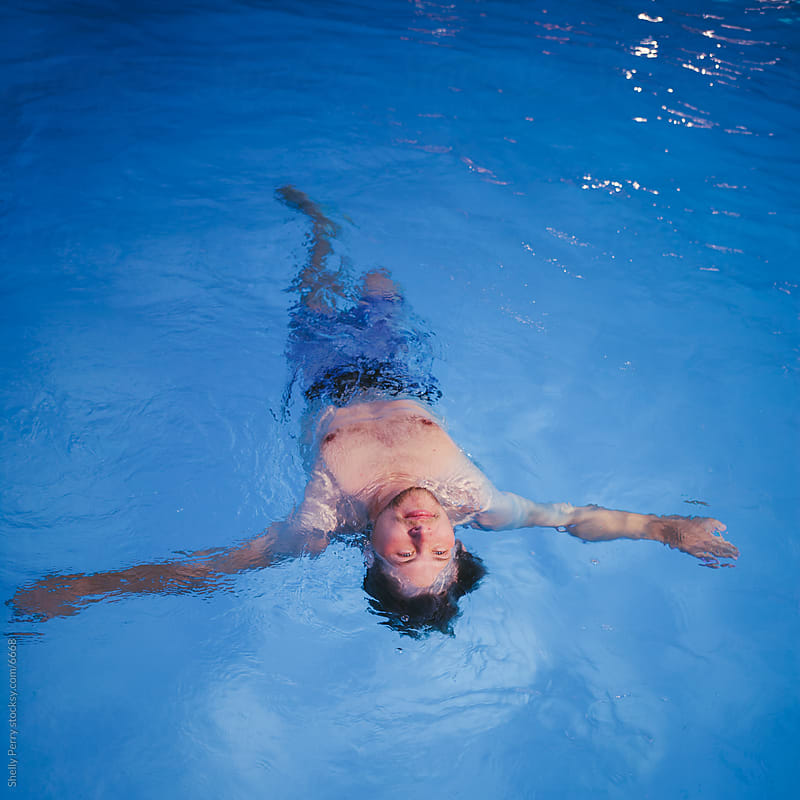 A Young Man Floats on His Back in a Blue Swimming Pool by Shelly Perry for Stocksy United