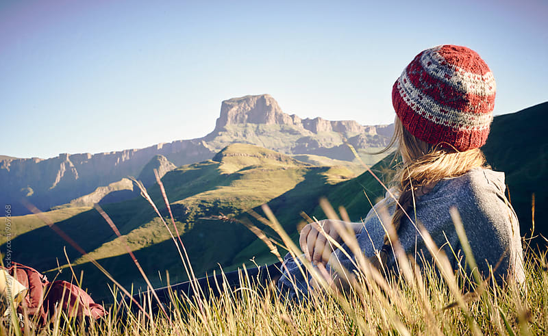 Female hiker with back pack taking a break in a field surrounded by mountains.  by Jacques van Zyl for Stocksy United