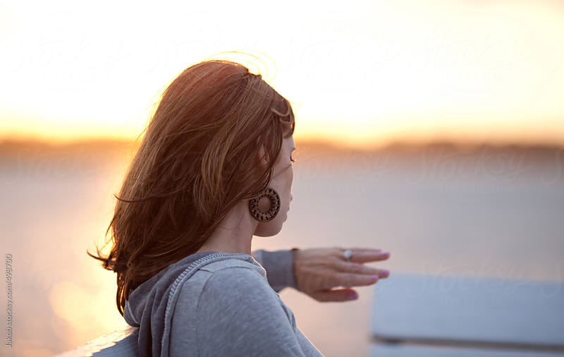 Newly engaged woman looking at her ring during beach sunset by Jakob for Stocksy United