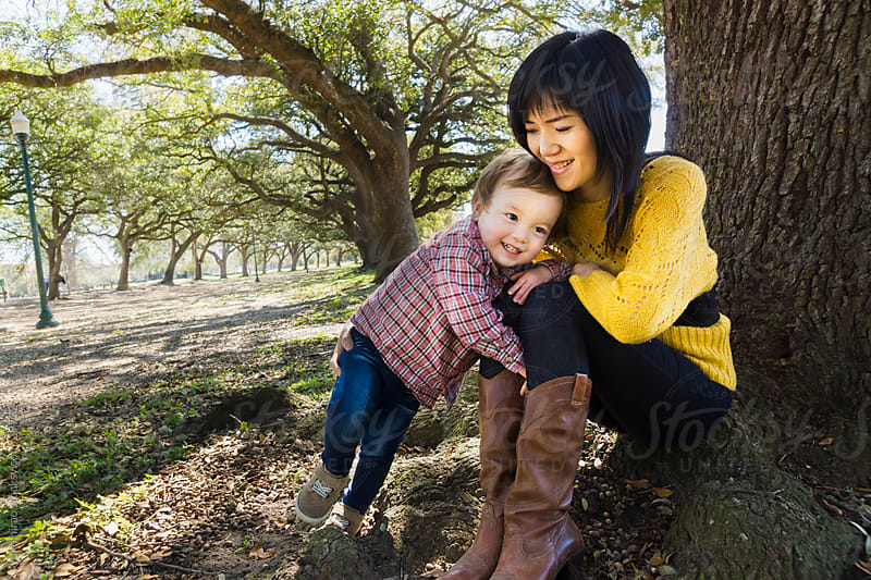 Smiling Asian mother and little boy, talking at park by yuko hirao for Stocksy United