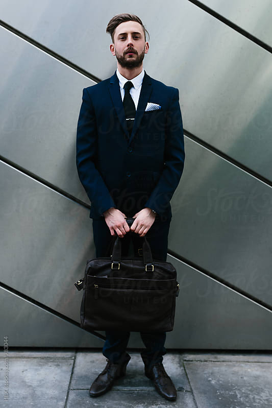 Trendy businessman standing against a black wall in the city by HEX . for Stocksy United