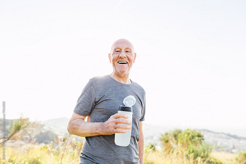 Portrait of a smiling senior man holding a bottle of water after workout.  by BONNINSTUDIO for Stocksy United