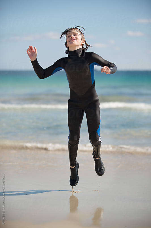 Boy in a wetsuit happily jumping at the beach by Angela Lumsden for Stocksy United
