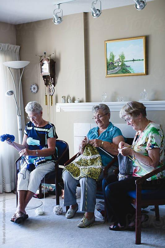 Group of senior women knitting together by Rob and Julia Campbell for Stocksy United