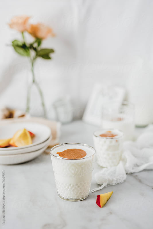 Yogurt with peach juice by Tatjana Ristanic for Stocksy United