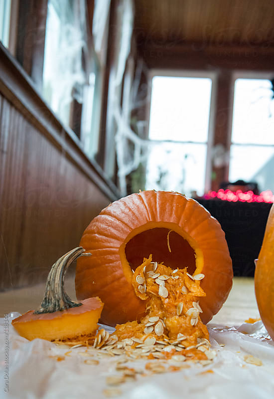 Pumpkin with innards hanging out is ready to be carved into a jack-o-lantern by Cara Dolan for Stocksy United