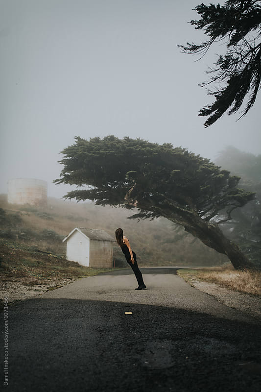 Woman Leaning In Front of Leaning Tree by Daniel Inskeep for Stocksy United