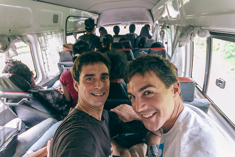Two male friends inside a bus full of people on travel by Alejandro Moreno de Carlos for Stocksy United