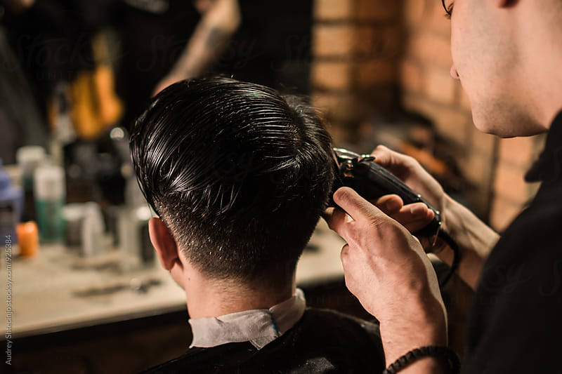 YOung barber working in vintage barber shop. by Audrey Shtecinjo for Stocksy United