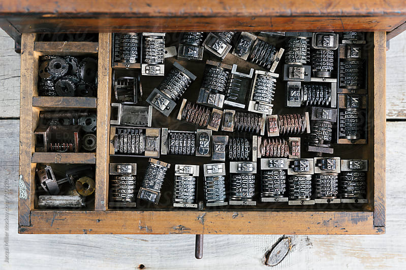 Old wood drawer filled with vintage metal numbering inserts for printer - from above by Jacqui Miller for Stocksy United