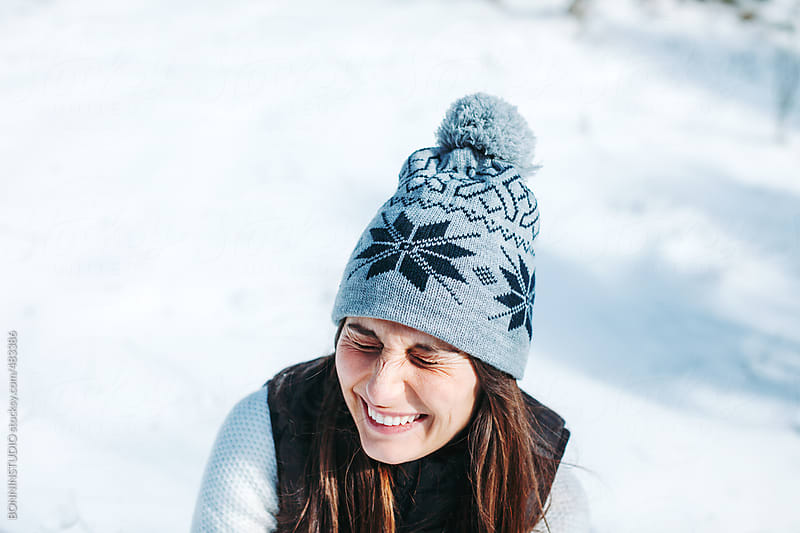 Portrait of a happy young woman on a snowy day. by BONNINSTUDIO for Stocksy United