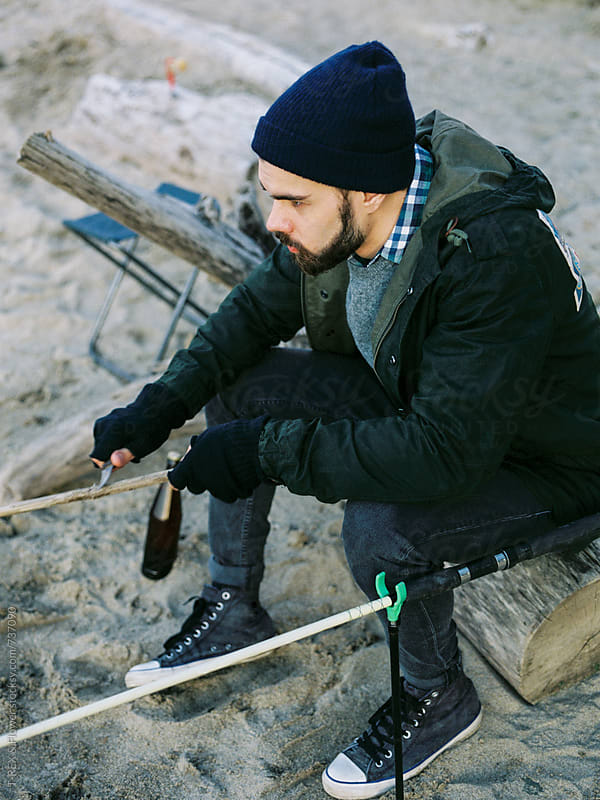 Fisherman sharpening a stick by Danil Nevsky for Stocksy United