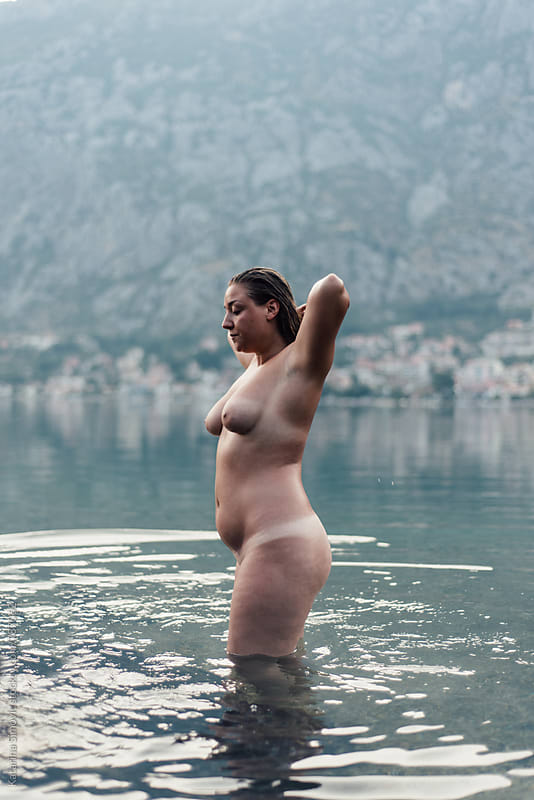 Young naked woman standing in the water by Kate & Mary for Stocksy United