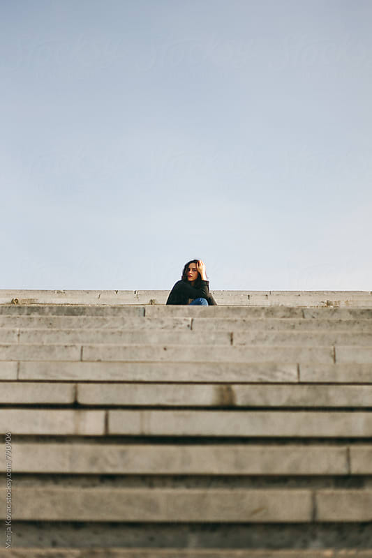 Young woman sitting on the stairs, looking at the camera - vertical by Marija Kovac for Stocksy United