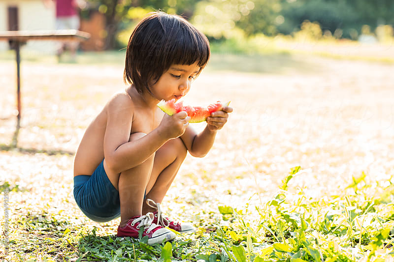 Asian Boy Eating Watermelon by Lumina for Stocksy United