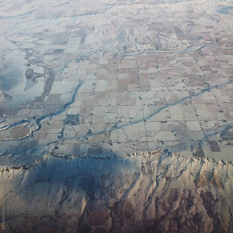 looking down at land while flying by Margaret Vincent for Stocksy United