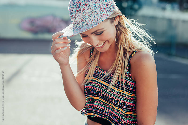 Beautiful young woman wearing cap smiling by Jacob Lund for Stocksy United