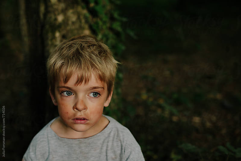 Close-up of young boy with reddish clay dust on his face playing in a forest. by Julia Forsman for Stocksy United