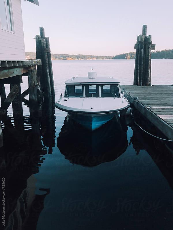 Little Blue Speed Boat Tied To A Dock by Luke Mattson for Stocksy United