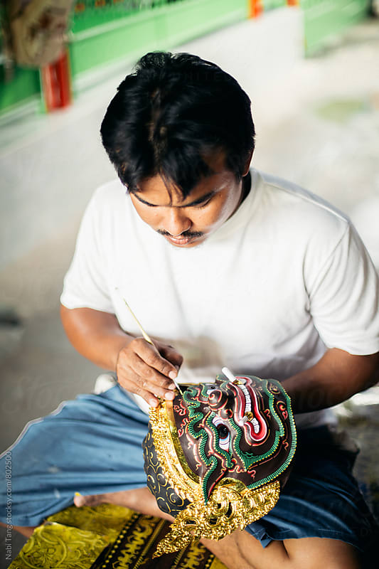 Young artist working on 'Hua Khon' traditional mask for Thai performing arts by Nabi Tang for Stocksy United