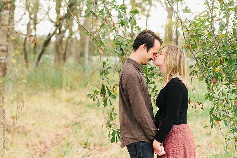 Cute Couple Laughing and Kissing Surrounded by Tree Branches by B. Harvey for Stocksy United