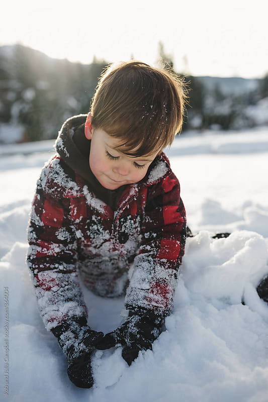 Happy kid playing in the snow by Rob and Julia Campbell for Stocksy United