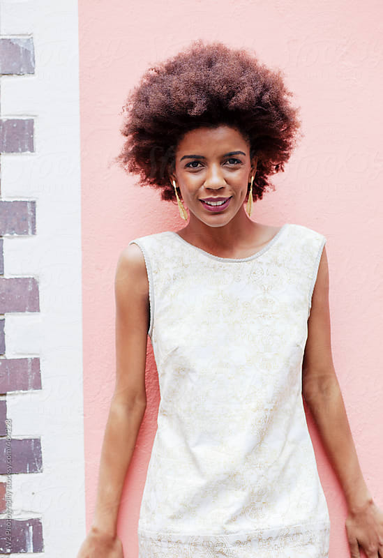 Model with afro posing in a summer dress by W2 Photography for Stocksy United