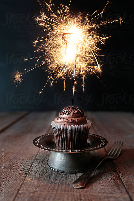 Chocolate cupcake with lit sparkler  by Sandra Cunningham for Stocksy United
