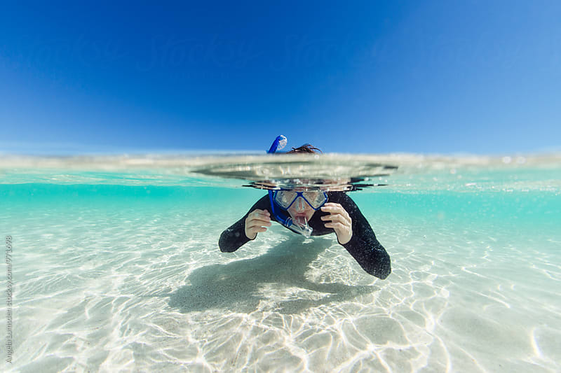 Boy wearing a snorkel set and wetsuit in clear shallow ocean water by Angela Lumsden for Stocksy United