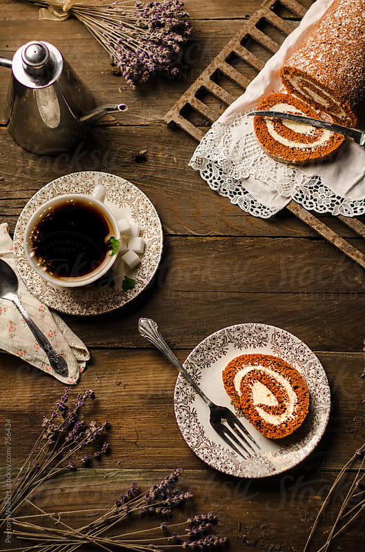 Pumpkin and Cream Cheese Spice Roll Accompanied by Black Coffee, Sugar, and Lavender on a Wood top by Peyton Weikert for Stocksy United