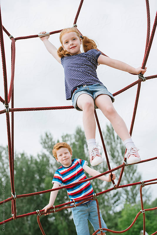 Children playing on a climbing frame in a park by Craig Holmes for Stocksy United