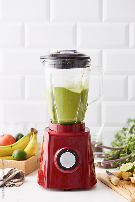 Delicious green smoothie with fruit in blender by Martí Sans for Stocksy United