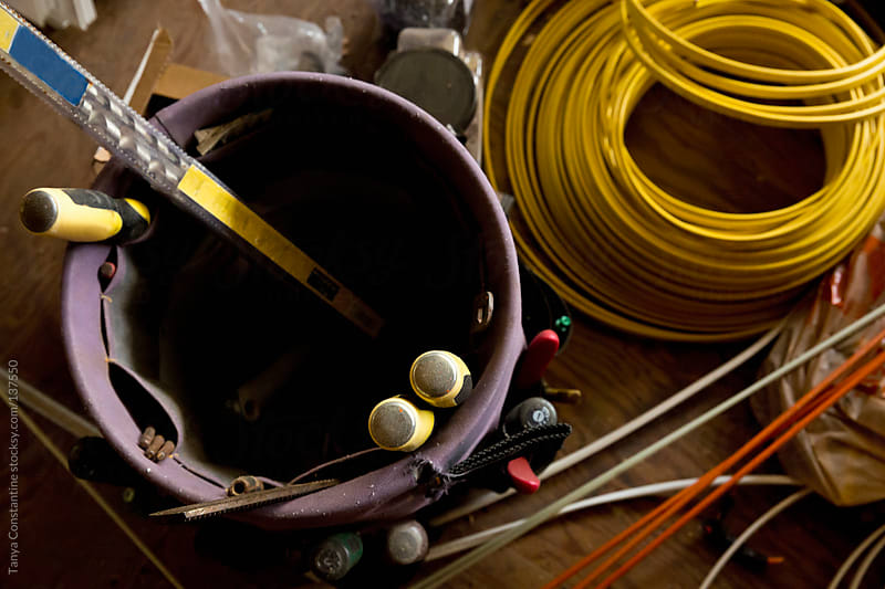 tools in a pail, and roll of electrical wiring by Tanya Constantine for Stocksy United