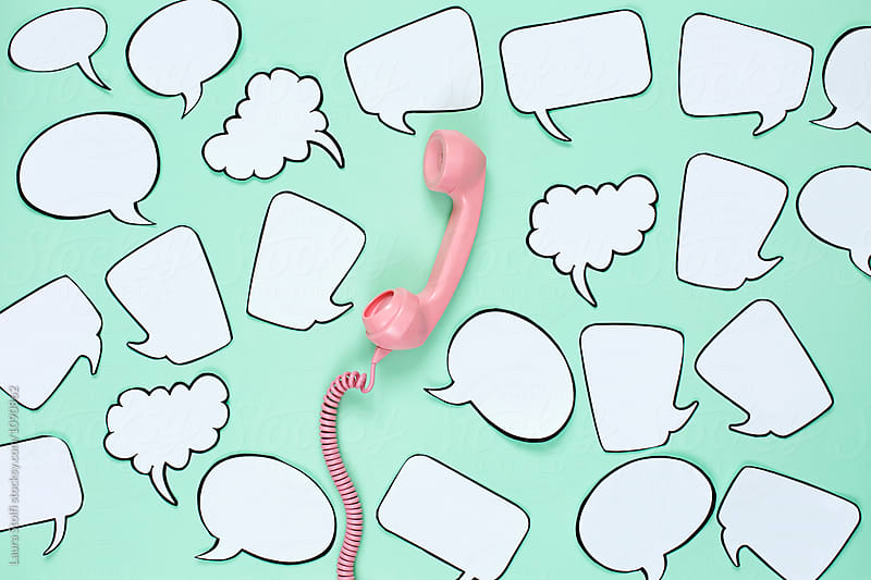 Random words around phone handset by Laura Stolfi for Stocksy United