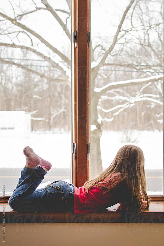 Girl lying beside a snowy window by Lindsay Crandall for Stocksy United