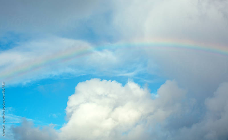 White cumulus clouds and a bright rainbow in the sky by Carolyn Lagattuta for Stocksy United