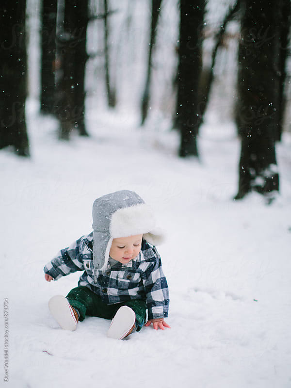 Baby boy touches snow in the woods by Dave Waddell for Stocksy United