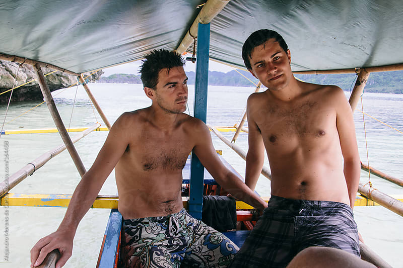 Two young male friends on a traditional boat on adventure travel by Alejandro Moreno de Carlos for Stocksy United