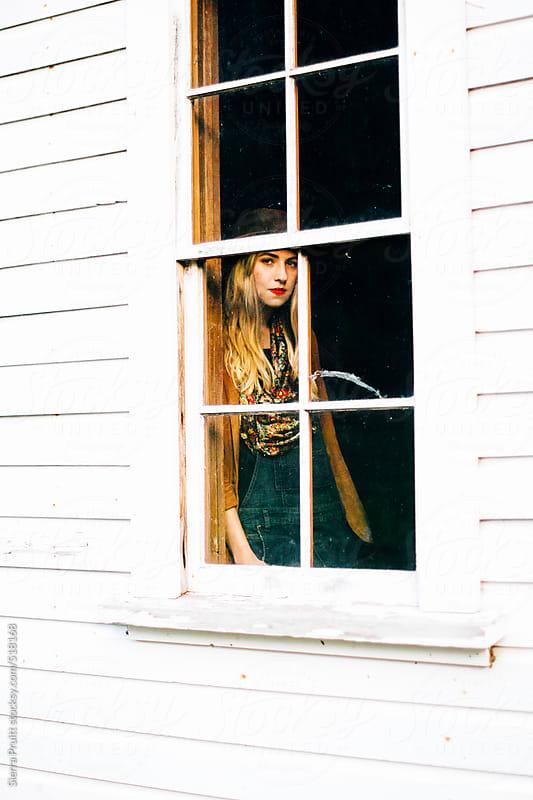 girl in a window by Sierra Pruitt for Stocksy United