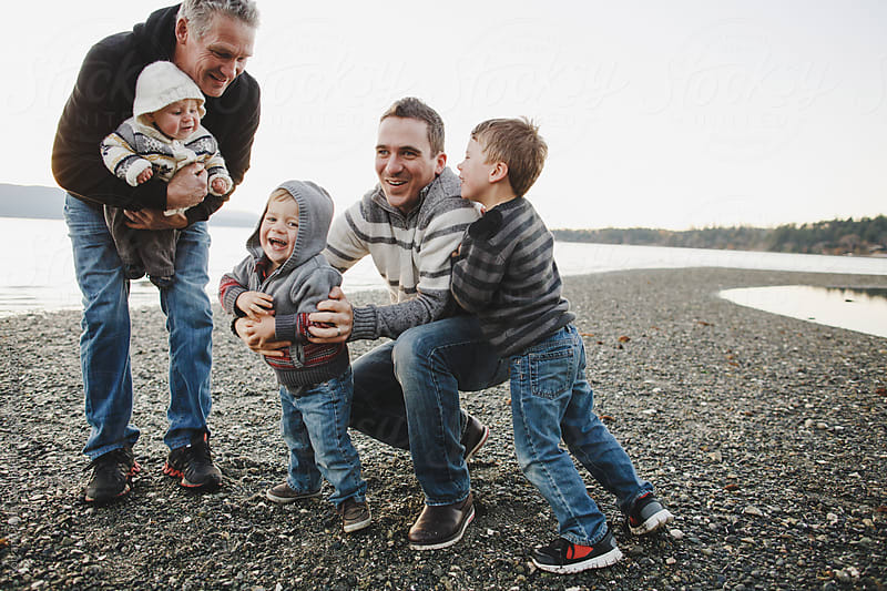 Multigenerational family at beach having fun together by Rob and Julia Campbell for Stocksy United