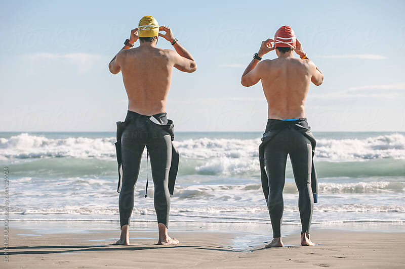 Two triathletes with wetsuit, cap and glasses getting ready for swim on a sunny day. by BONNINSTUDIO for Stocksy United