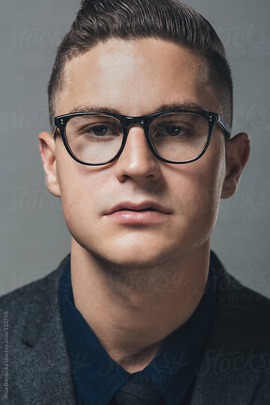 A portrait of a young man wearing black rimmed eyeglasses by Ania Boniecka for Stocksy United