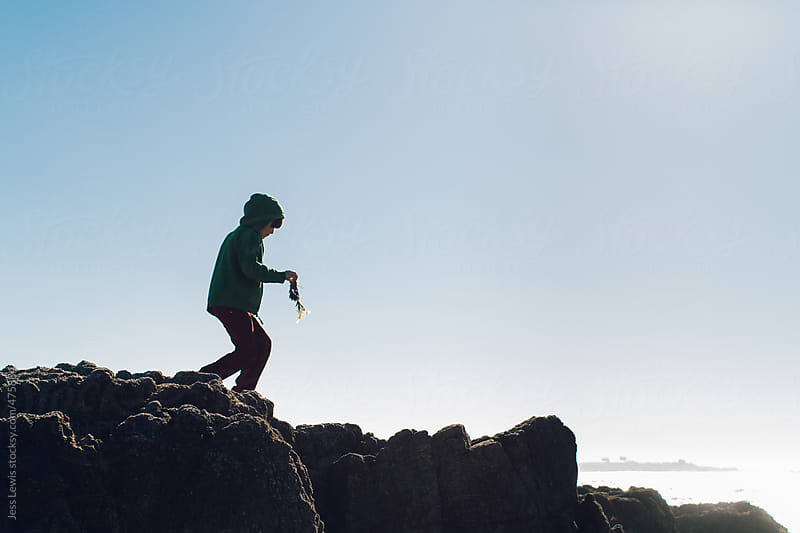 boy exploring coastal rocks at low tide by Jess Lewis for Stocksy United
