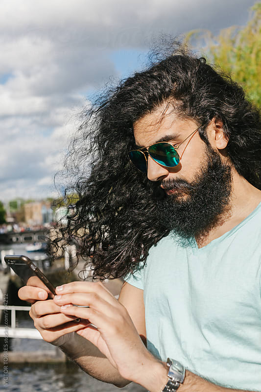 Muslim Young Man Using a Mobile Phone in the Street by VICTOR TORRES for Stocksy United