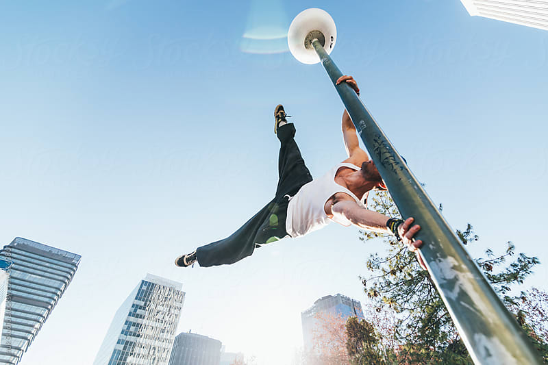 Man holding on to lamp post in mid air during a parkour training by Inuk Studio for Stocksy United