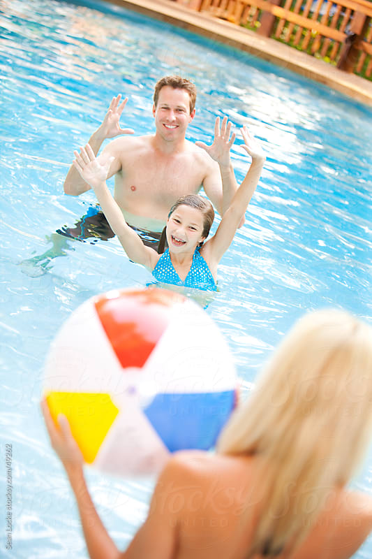 Swimming: Playing Beach Ball with Parents in the Pool by Sean Locke for Stocksy United