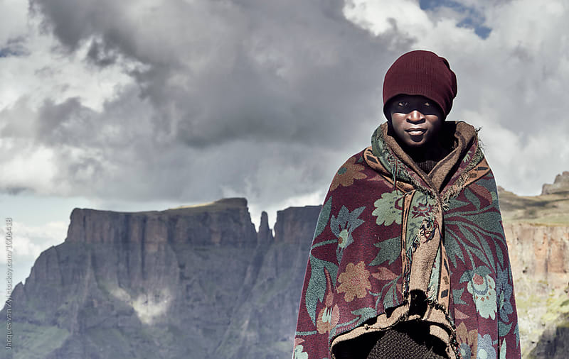 A portrait of a black Basotho shepherd wrapped in a traditional blanket. by Jacques van Zyl for Stocksy United