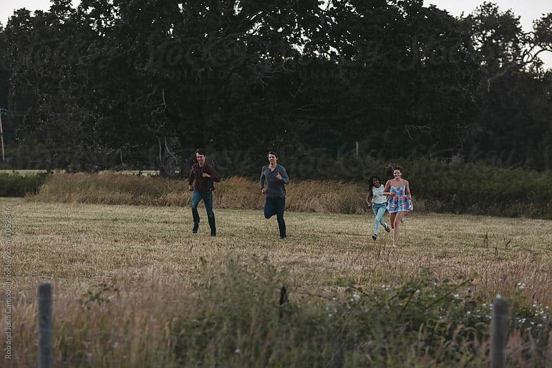 Young friends running in field during  summer road trip together by Rob and Julia Campbell for Stocksy United