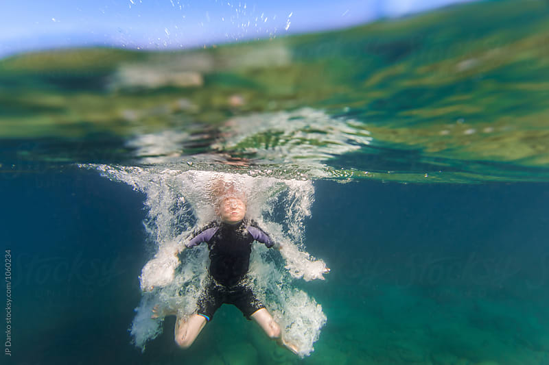 Underwater Splash and Bubbles of Boy Jumping Into Summer Lake From Water Trampoline At Cottage by JP Danko for Stocksy United